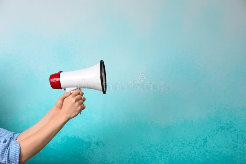 H?llande megafon f?r kvinna p? f?rgbakgrund royaltyfri fotografi