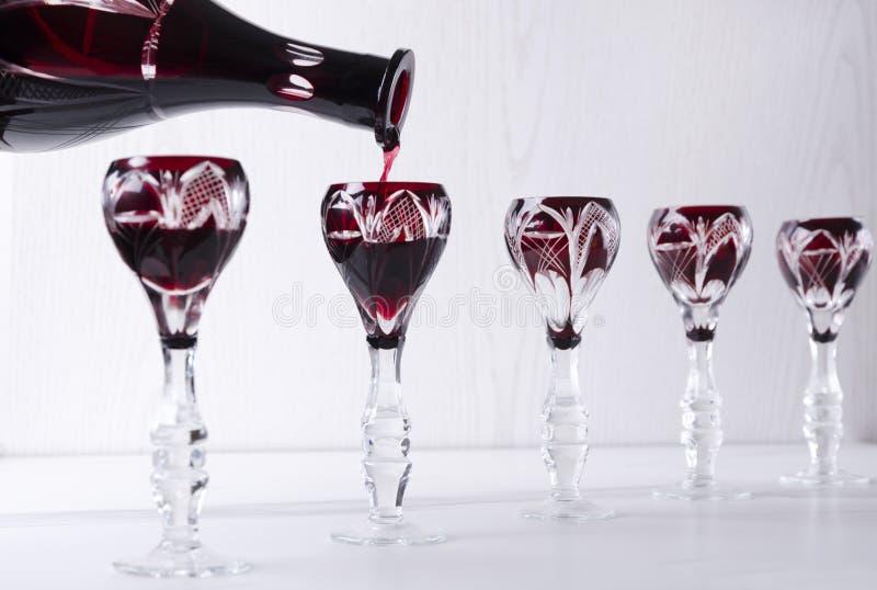 H?llande r?d bitter alkoholdryck in i tappningexponeringsglas Begrepp av buffématställen royaltyfria bilder