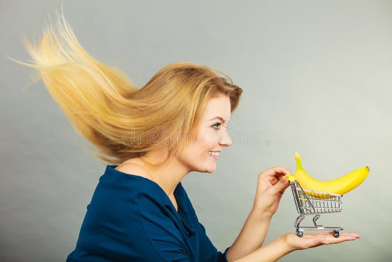 H?llande shoppingvagn f?r kvinna med bananen inom royaltyfri fotografi