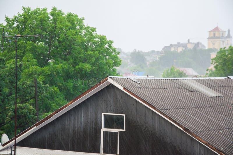 H?llregn i sommaren dusch Del av huset och taket Mot bakgrunden royaltyfri bild