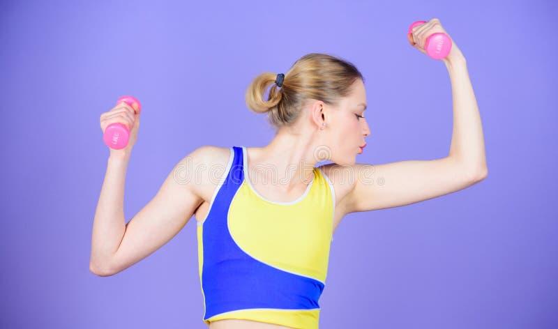 H?lsa bantar Sportframg?ng Starka muskler och makt Sportig kvinnautbildning i idrottshall Lycklig kvinnagenomk?rare med skivst?ng arkivfoton
