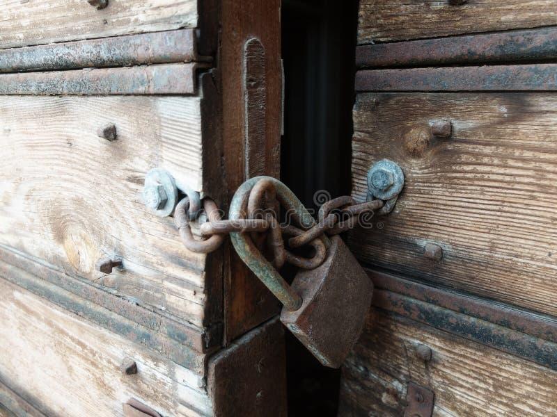 H?lzern verwitterte die antiken Tore, die mit Vorh?ngeschlo? geschlossen wurden lizenzfreie stockbilder