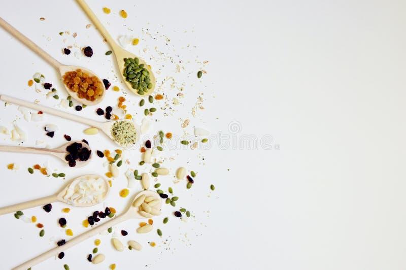 H?lzerne L?ffel auf der linken Seite, voll von den Samen und von den Getreide stockfotografie