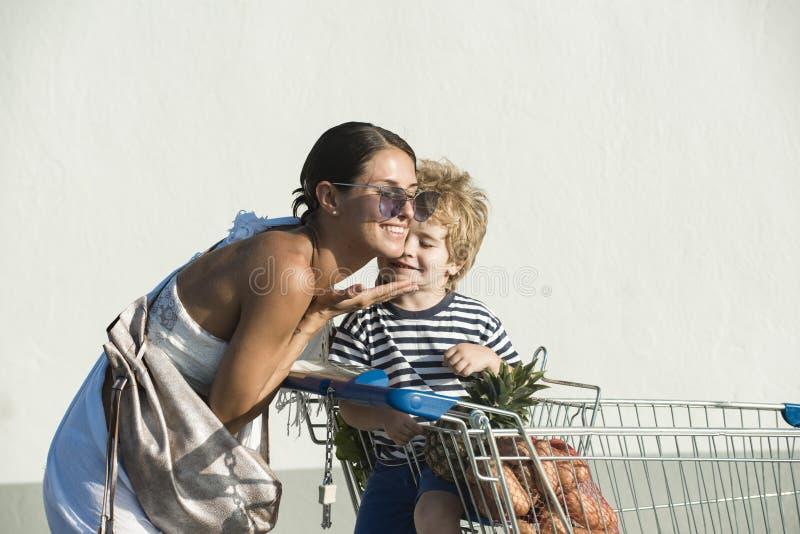H?lzerne Puppefamilie gehen zum Supermarkt mit MetallEinkaufswagen Glückliches Elternteil mit nettem Sohn gehen Mutter, die Einka lizenzfreie stockfotografie