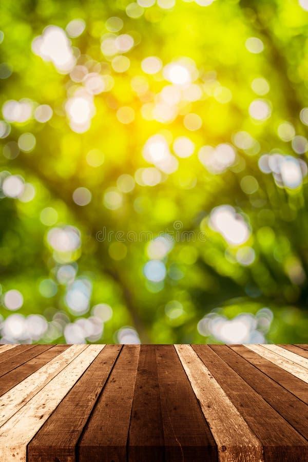h?lzerne Tabelle und gr?nes Baum bokeh lizenzfreie stockfotografie