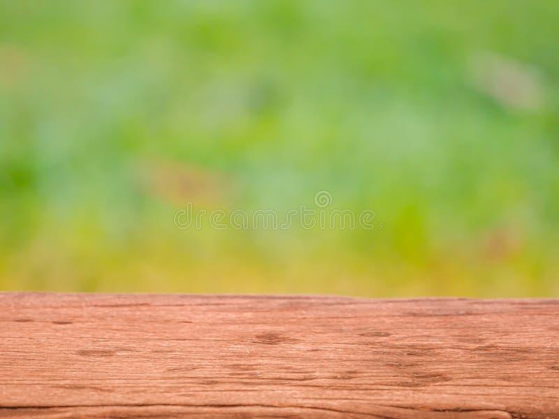 H?lzerne Tischplatte auf Unsch?rfezusammenfassungsgr?n vom Garten F?r Montageproduktanzeige oder Designschl?sselsichtplan lizenzfreies stockfoto