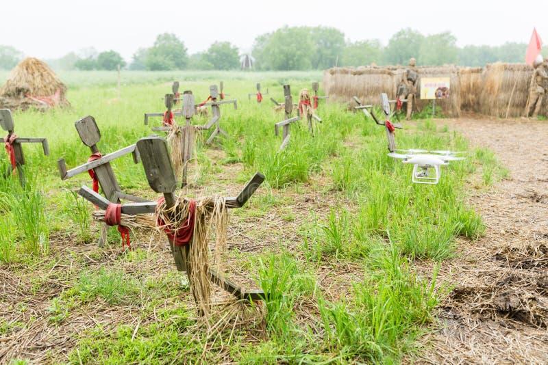 H?lzerne Vogelscheuchen, die auf dem Feld im Dorf stehen Folgender fliegender Hubschrauber lizenzfreie stockfotografie