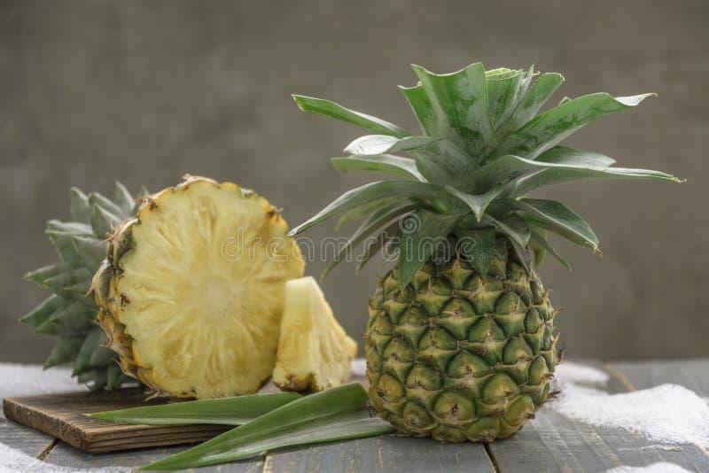 H?lzernes Brett mit frischer geschnittener Ananas auf Tabelle stockfotografie