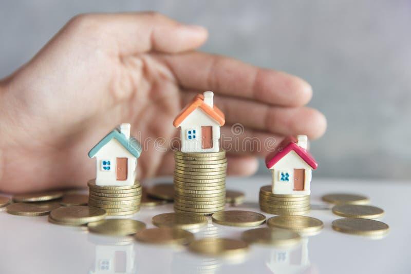H?nde als sch?tzendes Dach ?ber einem kleinen Haus, einem Immobiliarversicherungs- und Sicherheitskonzept Sch?tzende Geste des Ma lizenzfreie stockbilder