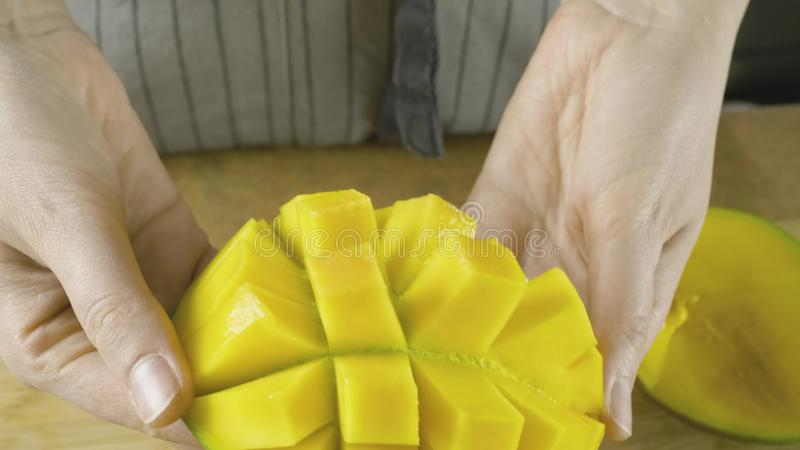 H?nde der jungen Frau breitet cutted gelbe Mango im Zeitlupeabschlu? herauf Video in 4K aus stockfotografie