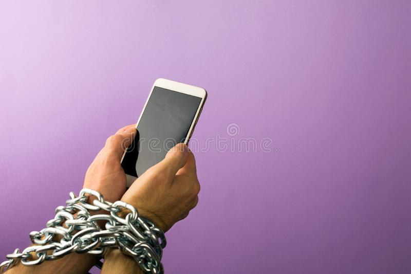 H?nde gebunden mit metallischer Kette am Smartphone lizenzfreie stockfotografie