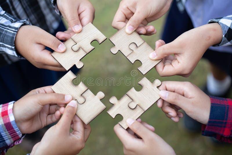 H?nde von den verschiedenen Leuten, die Puzzlen, das gesetzte Team zusammenbauen, stellt das Suchen nach rechtem Match, Hilfsunte stockfotos