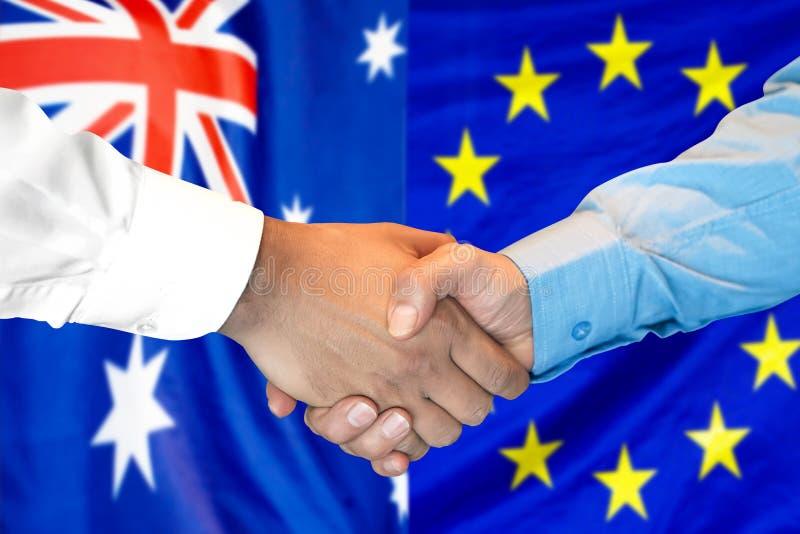 H?ndedruck auf Australien- und Gemeinschaftsflagge Hintergrund stockfoto