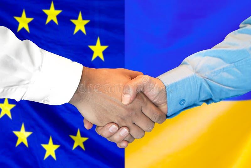 H?ndedruck Hintergrund auf der Europ?ischen Gemeinschaft und Ukraine Flagge stockbilder