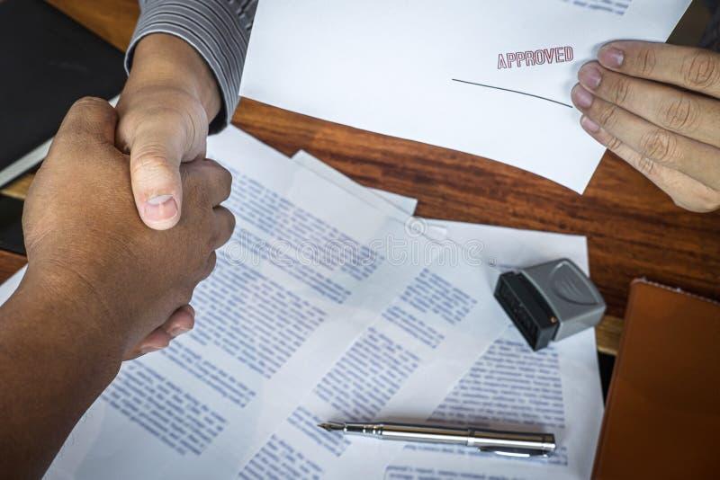 H?nder av aff?rsmannen som skakar efter f?r att avsluta sig underteckning och st?mpla p? pappersdokument f?r att godk?nna ?verens royaltyfri bild