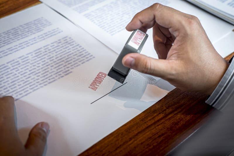 H?nder av aff?rsmanst?mpeln p? det pappers- dokumentet som godk?nner ?verenskommelse f?r avtal f?r aff?rsinvestering arkivbilder