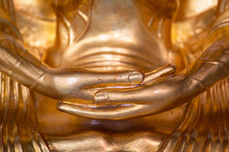 H?nder av den guld- Buddhastatyn arkivbilder