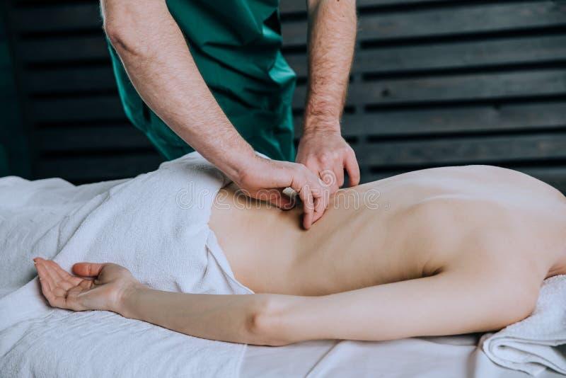 H?nderna av en manlig mass?r som han g?r masserar baksidan av en kvinna i den lumbala regionen royaltyfri foto