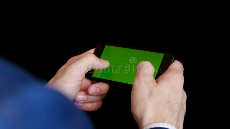 H?nderna av m?n med ett tegelstenplan att rymma en smartphone p? en svart bakgrund royaltyfria foton