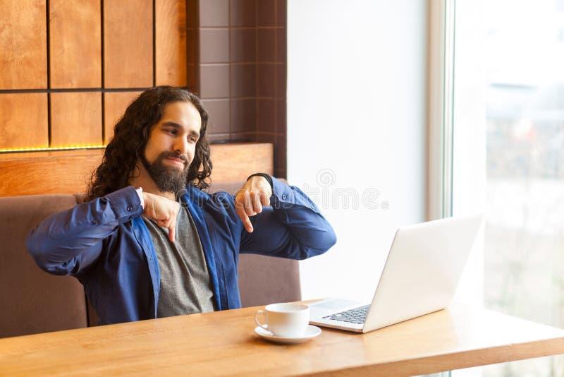 H?r och just nu Stående av den ilskna stiliga unga ledaremanfreelanceren i tillfällig stil som sitter i kafé och talar i bärbar d royaltyfri bild