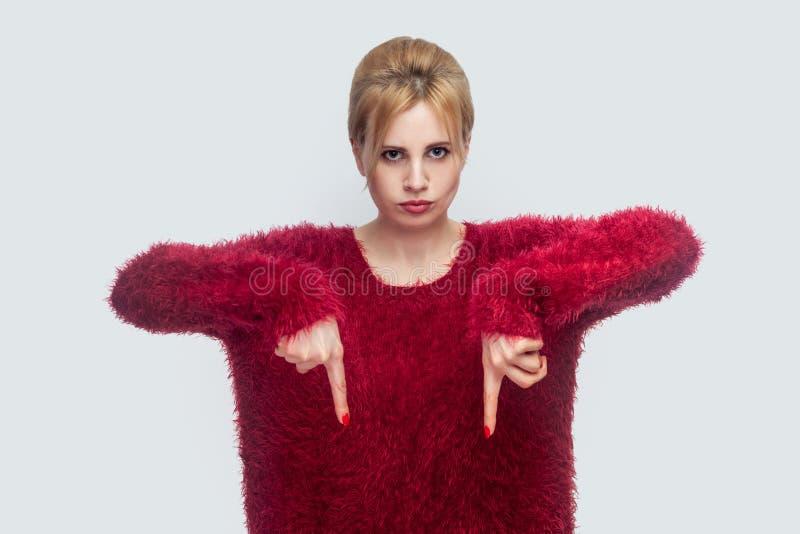 H?r och just nu Stående av den ilskna unga blonda kvinnan, i rött anseende och att befalla för blus för att vara här snabbt som m royaltyfri bild