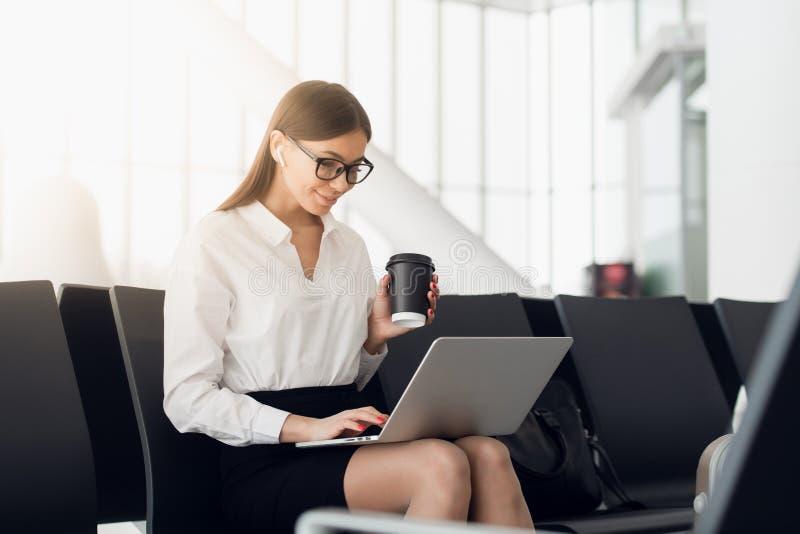 H?rlig aff?rskvinna som arbetar p? b?rbara datorn, medan v?nta p? hennes flyg i en flygplats royaltyfri foto