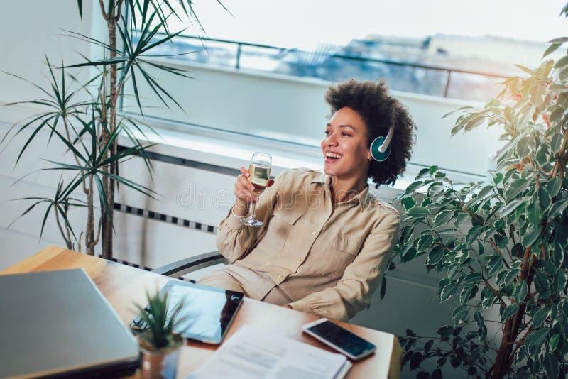 H?rlig afrikansk amerikankvinna som kopplar av och lyssnar till musik genom att anv?nda headphonen som dricker vin royaltyfria bilder