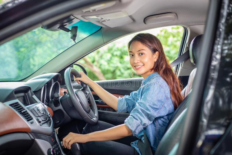 H?rlig asiatisk kvinna som ler och tycker om k?rning av en bil p? v?gen f?r lopp royaltyfri foto