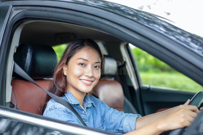H?rlig asiatisk kvinna som ler och tycker om k?rning av en bil p? v?gen f?r lopp royaltyfria foton