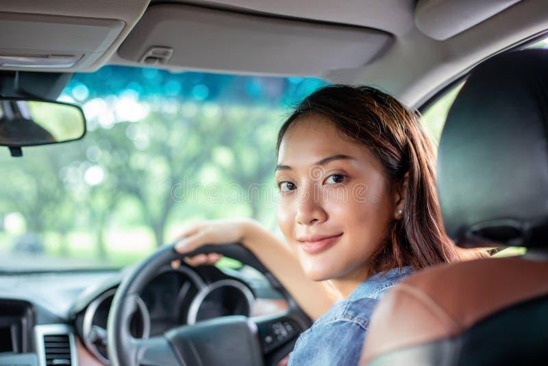 H?rlig asiatisk kvinna som ler och tycker om k?rning av en bil p? v?gen f?r lopp arkivfoton