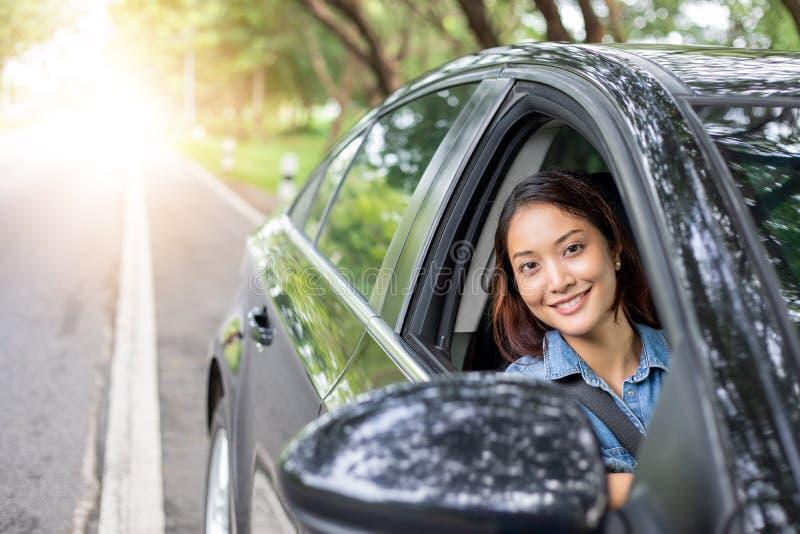 H?rlig asiatisk kvinna som ler och tycker om k?rning av en bil p? v?gen f?r lopp arkivbild