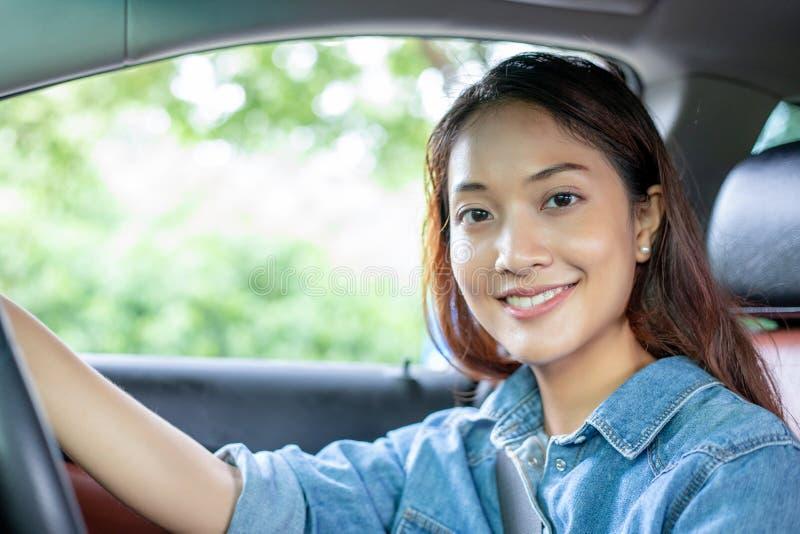 H?rlig asiatisk kvinna som ler och tycker om k?rning av en bil p? v?gen f?r lopp fotografering för bildbyråer