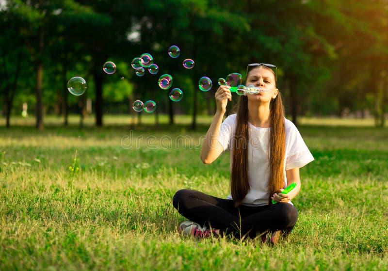 H?rlig flicka f?r ung kvinna med att spela bubblaballonger i tr?dg?rdferien royaltyfri fotografi