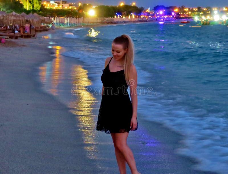 H?rlig flicka i en svart kl?nning vid havet royaltyfri bild