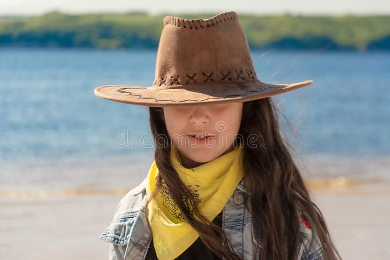 H?rlig flicka med l?ngt svart h?r i en cowboyhatt p? stranden p? en solig dag royaltyfri foto