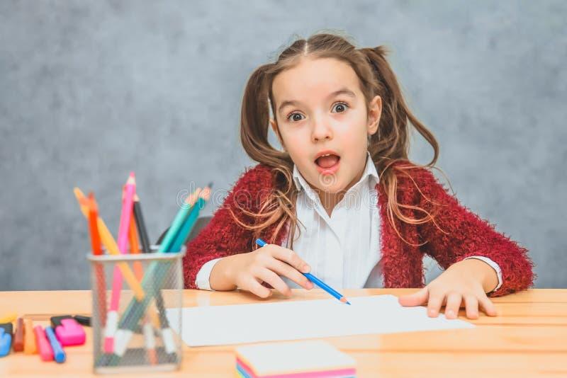 H?rlig flicka p? gr? bakgrund Att ta en blå blyertspenna ser in i kameran På tabellen finns det rosenfärgat royaltyfri foto