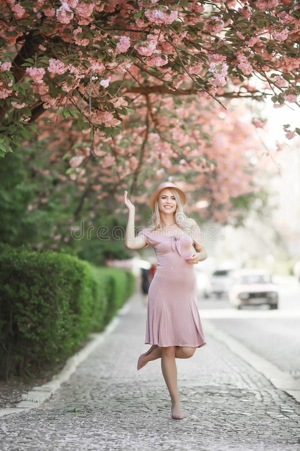 H?rlig flicka som poserar i den rosa persikan och Sakura Flowers Blooming Garden Ungt attraktivt le f?r kvinna som poserar royaltyfri bild