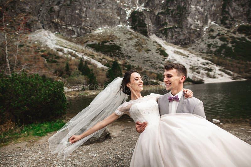 H?rlig gifta sig photosession Brudgummen cirklar hans unga brud, p? kusten av sj?n Morskie Oko poland royaltyfri bild