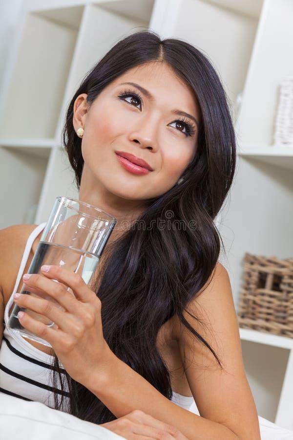 H?rlig kinesisk asiatisk kvinna som dricker exponeringsglas av vatten arkivbilder