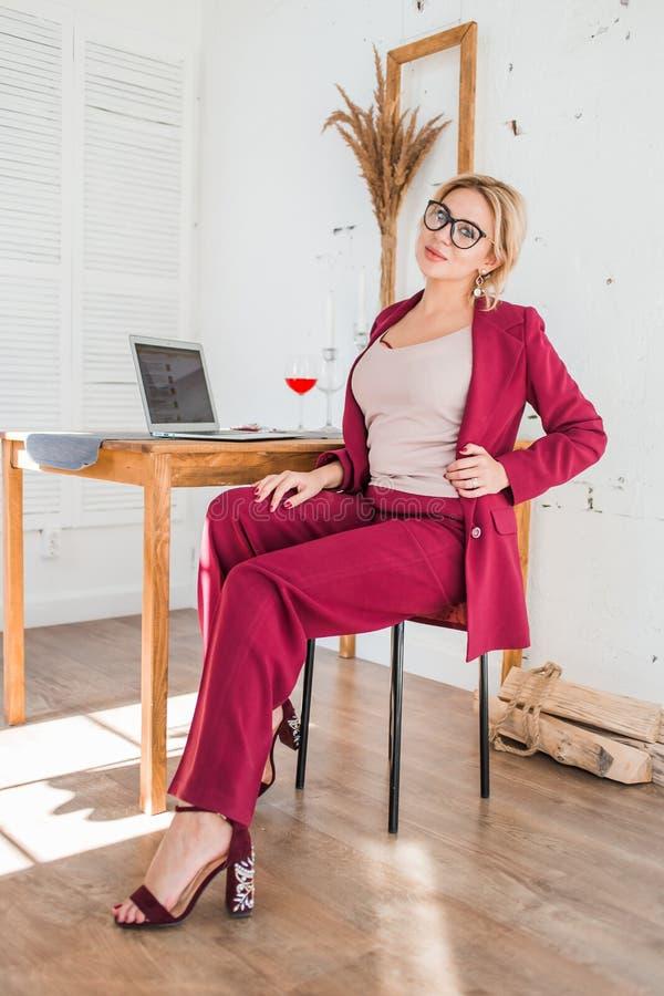 H?rlig klyftig aff?rskvinna som sitter p? tabellen p? arbetsstationen med b?rbara datorn arkivbilder
