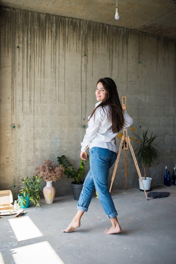 H?rlig konstn?r f?r ung dam i den vita skjortan som barfota dansar i hennes bohemiska konstn?rliga studiovind royaltyfri foto