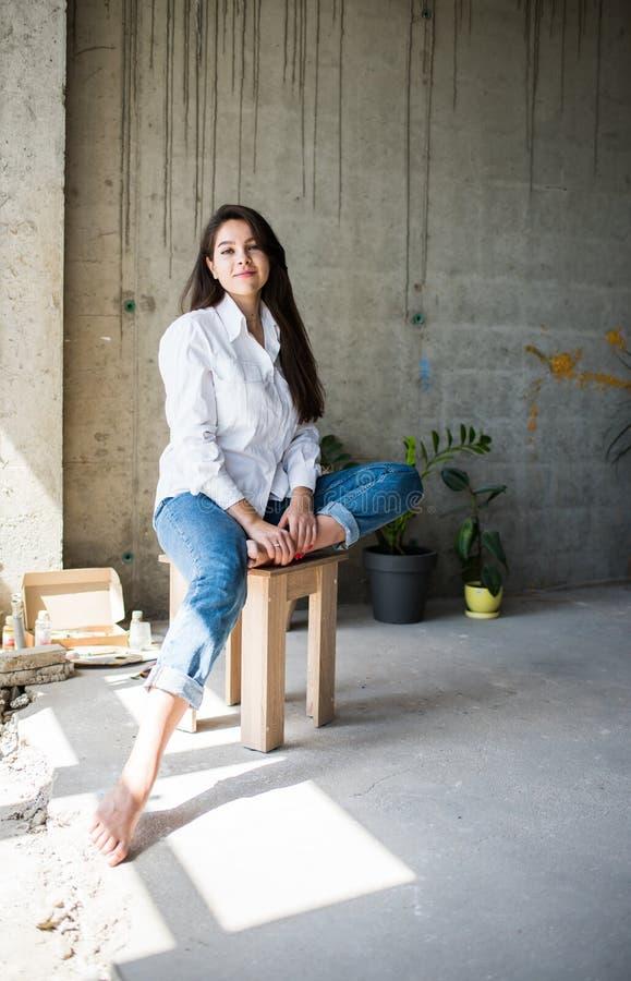 H?rlig konstn?r f?r ung dam i den vita skjortan som barfota sitter i hennes bohemiska konstn?rliga studiovind arkivbild