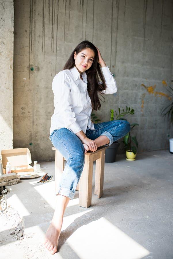 H?rlig konstn?r f?r ung dam i den vita skjortan som barfota sitter i hennes bohemiska konstn?rliga studiovind royaltyfria bilder