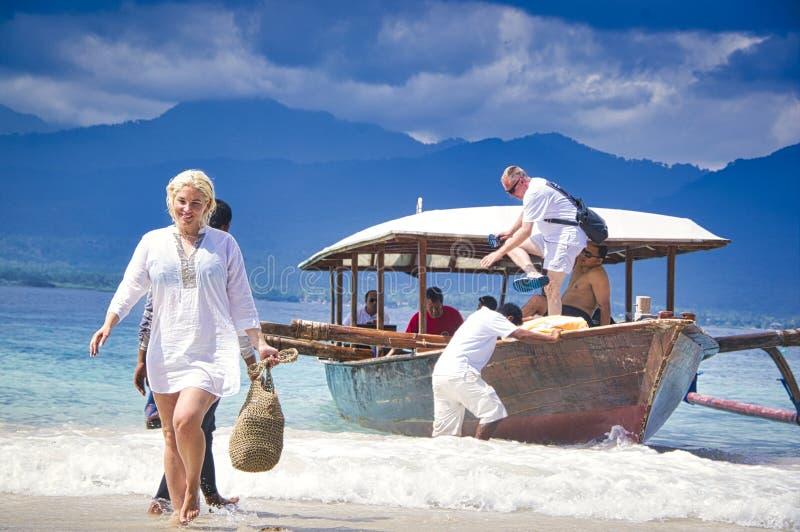 H?rlig kvinna i en vit kl?nning som g?r p? stranden Avkopplad kvinna som andas ny luft, emotionell sinnlig kvinna n?ra havet, arkivfoton