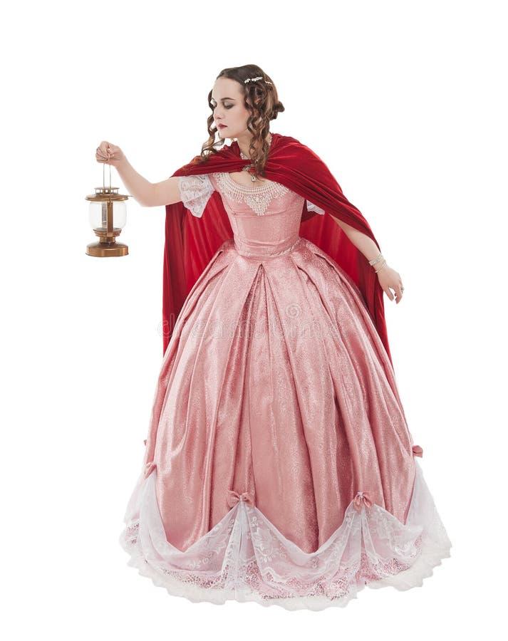 H?rlig kvinna i gammal historisk medeltida kl?nning med den isolerade lyktan royaltyfri bild