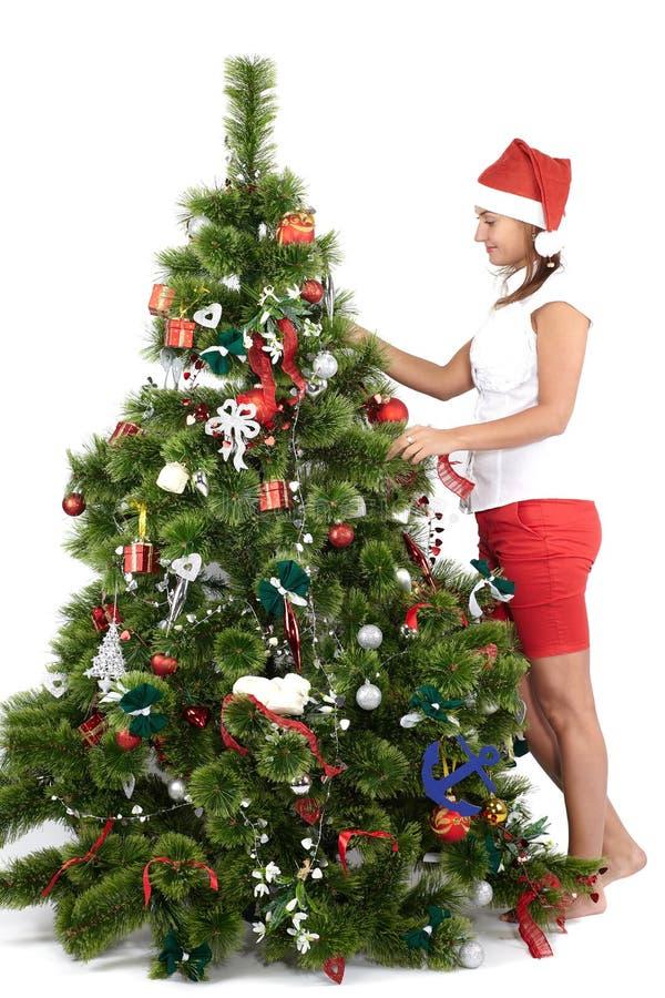 H?rlig kvinna i jultomtenlock som dekorerar julgranen royaltyfria foton