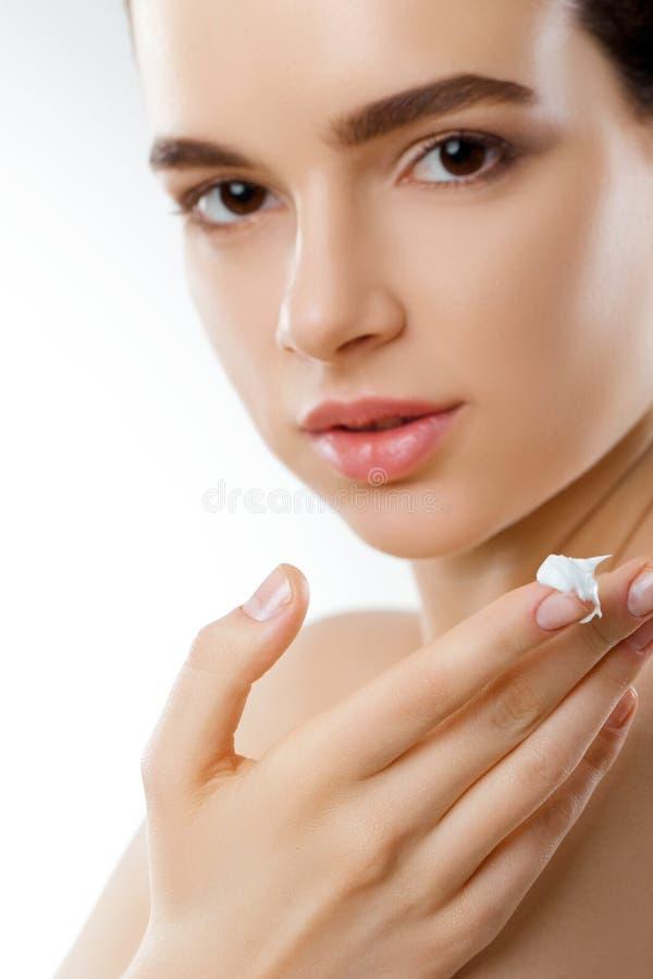H?rlig kvinna med framsidakr?m Hudskydd Skincare Spa En ung kvinnlig rymmer att fukta kr?m royaltyfri foto