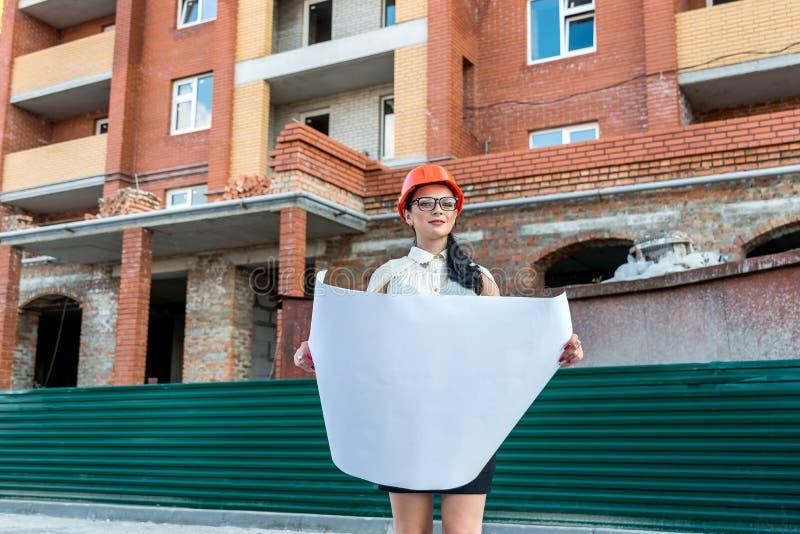 H?rlig kvinna p? konstruktionsplatsen som ser ritningen arkivfoton
