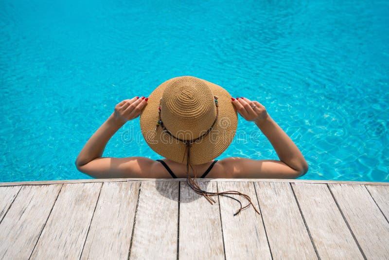 H?rlig kvinna som tycker om i simbass?ngen Flicka som kopplar av p? p?l i varm solig dag Idyllisk sommarferie glass kvinna f?r r? arkivbilder
