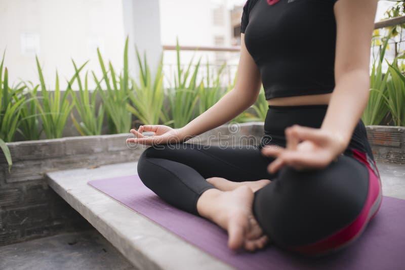 H?rlig kvinna som utomhus g?r yoga p? en takterrass arkivbilder